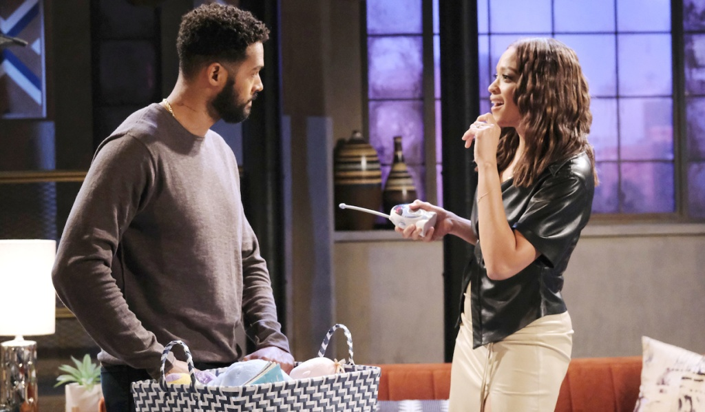 At home, Eli looks seriously at Lani who holds a baby monitor and grins on Days of Our Lives