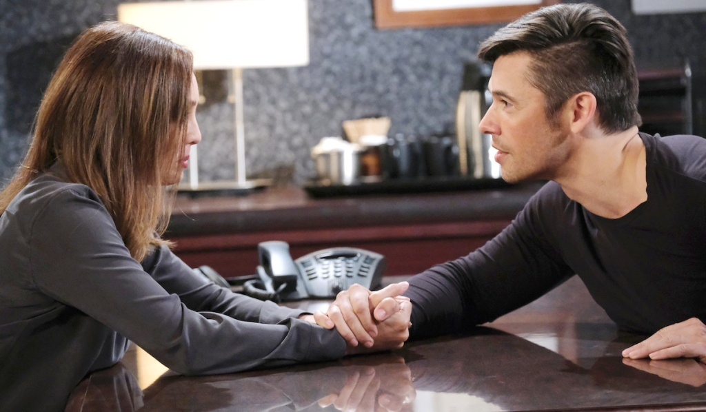 Gwen and Xander clasp hands across the interrogation room table on Days of Our Lives