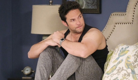 In sweats and a tank top, a stressed looking Jake sits up in bed. His arms rest on his bent knees. His hands are clasped.