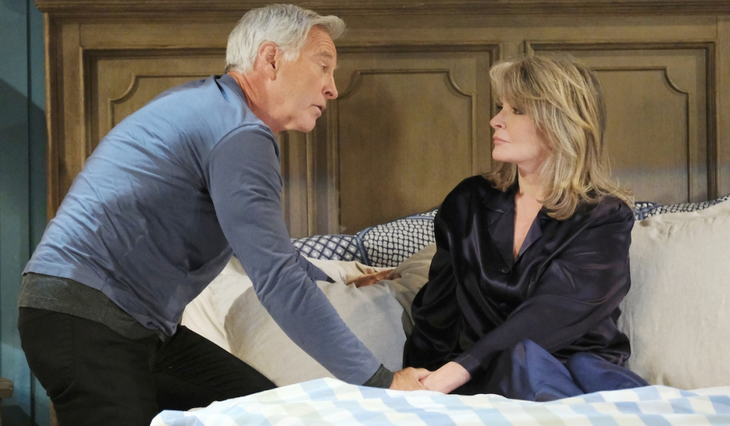 John leans on the bed close to Marlena to sits and looks at him on Days of Our Lives