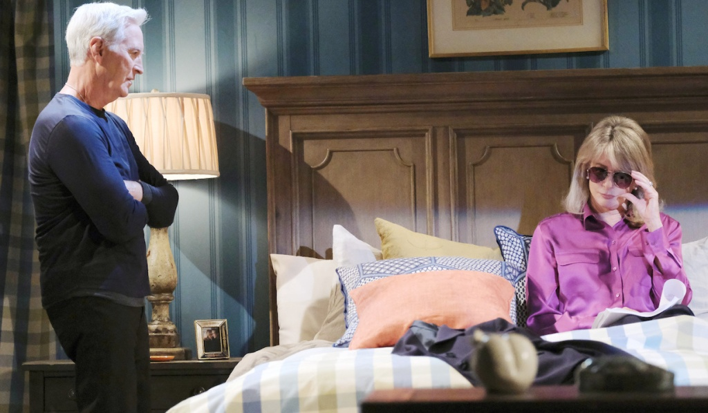 John crosses his arms, staring at MarDevil, who sits on the bed wearing sunglasses on Days of Our Lives