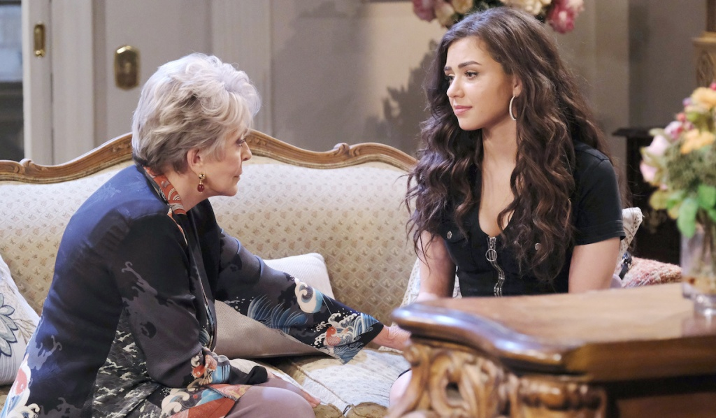 Julie and Ciara sit facing each other on the Horton House couch on Days of Our Lives