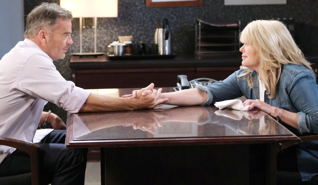 Justin and Bonnie reach across the table to clasp hands in the interrogation room on Days of Our Lives