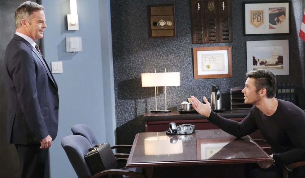 Justin stands stoically in the interrogation room. Xander uses one hand to make a point while the other is handcuffed to a chair on Days of Our Lives