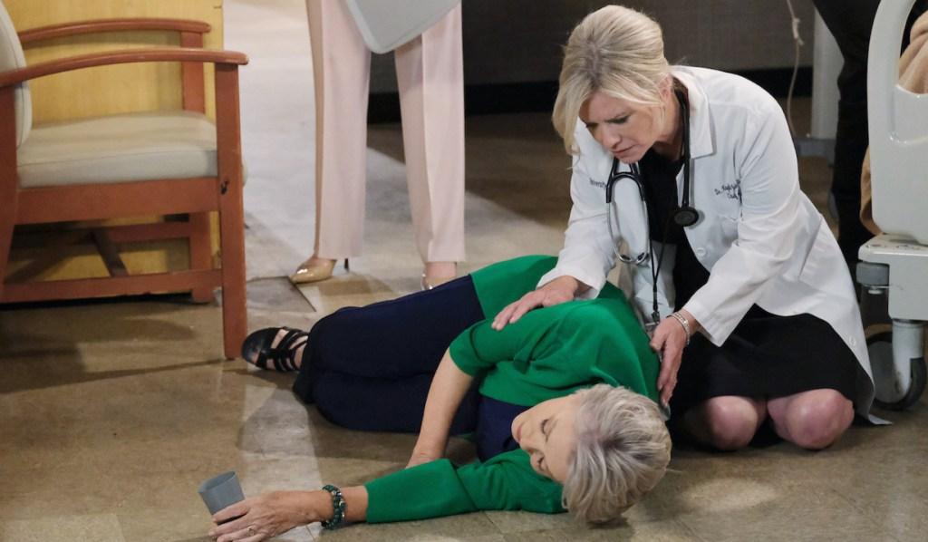 Kneeling Kayla bends over Julie lying on the hospital floor during Days of Our Lives