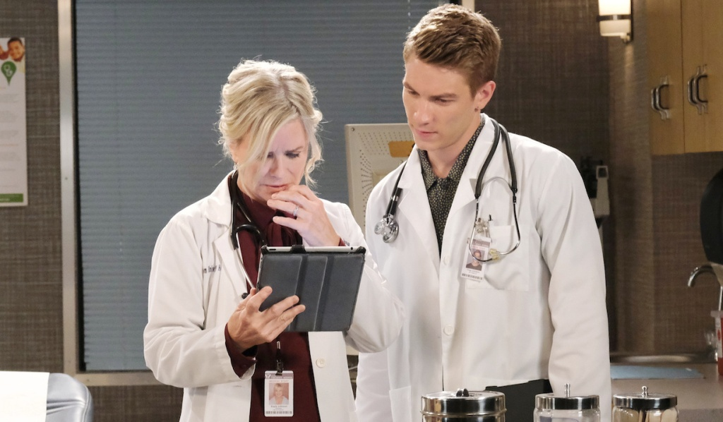 In lab coats, Kayla and Tripp pour over a tablet at the hospital on Days of Our Lives