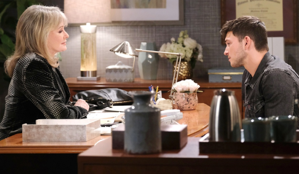 Marlena and Ben sit across from each other at her desk on Days of Our Lives