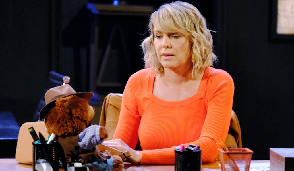 Nicole thoughtfully watches Duke on her desk at Basic Black on Days of Our Lives