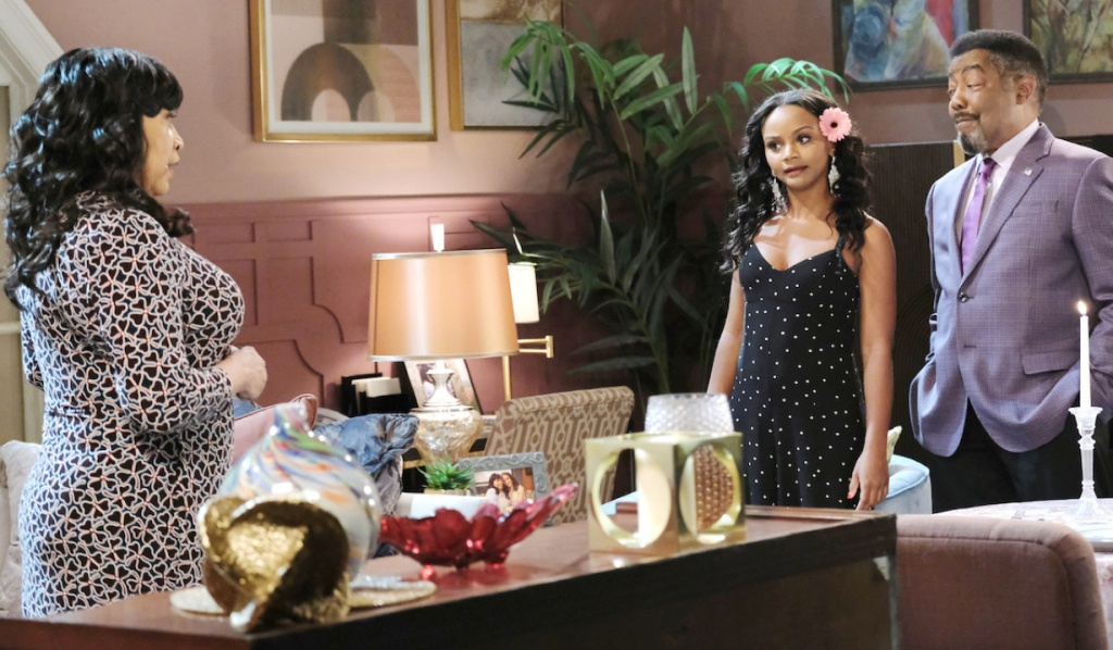 In her apartment, Paulina stands across the room from Chanel and Abe on Days of Our Lives