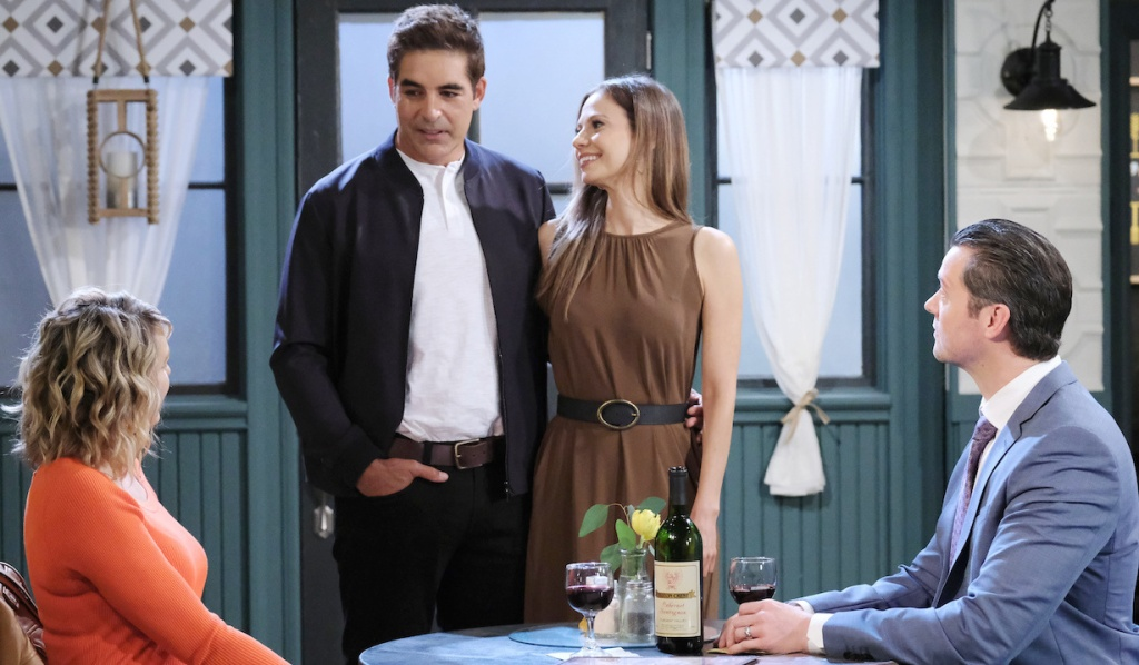 Rafe and Ava stand arm in arm at Nicole and EJ's table at Julie's Place on Days of Our Lives