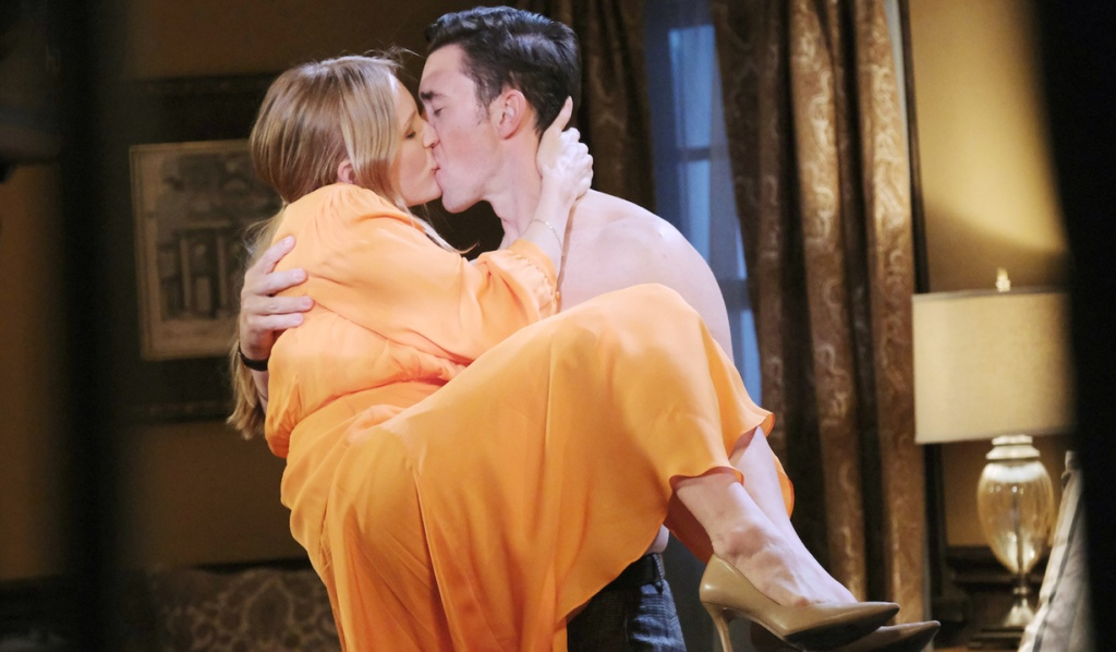 A shirtless Chad carries Abby while kissing her on Days of Our Lives
